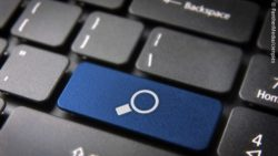 A black keyboard with a blue key with a magnifying glass on it; copyright: PantherMedia/cienpies