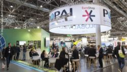 Exhibition area in an exhibition hall with stands and people; copyright: Messe Düsseldorf/ctillmann