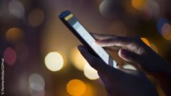 Hand using a smartphone in the dark; copyright: PantherMedia/LDProd